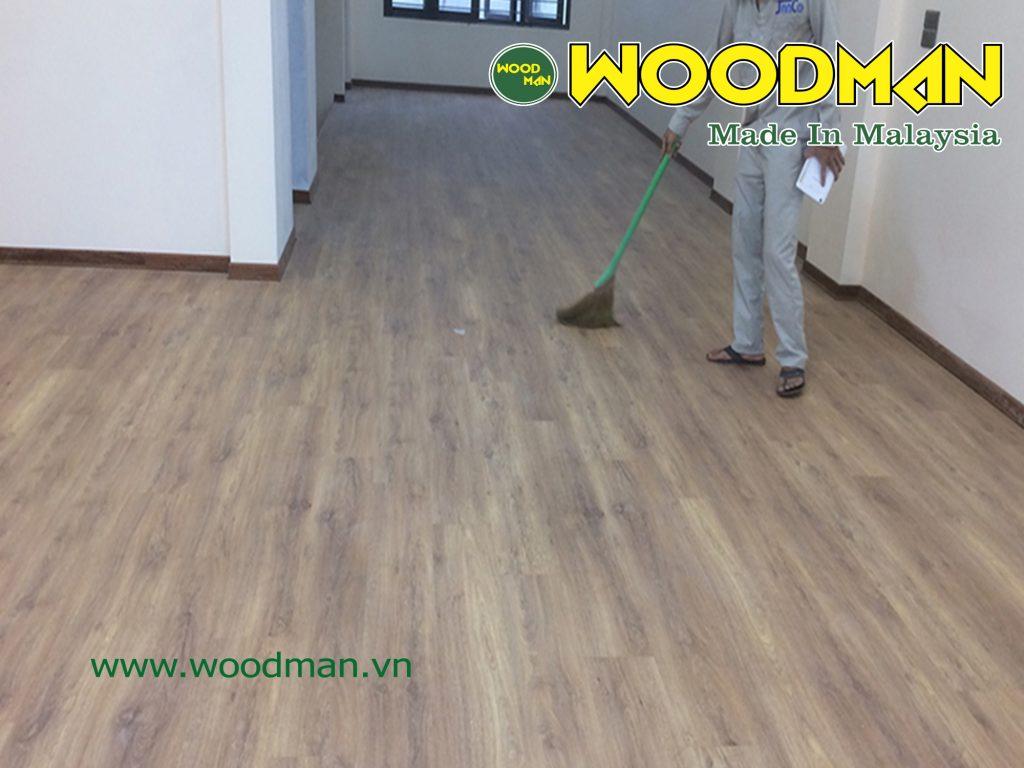 Nhân viên kỹ thuật vệ sinh sàn gỗ Woodman sau thi công.